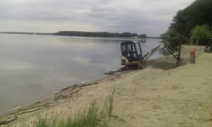 Миниэкскаватор работает на пляже