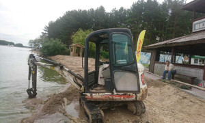 Миниэкскаватор чистит пляж